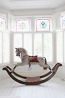 Antique rocking horse in bay window with stained glass London