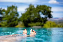 Woman Feet Floating in Infinity Pool in the Countryside