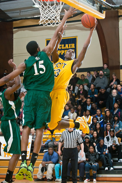 Lathan Goumas | MLive.com..February 22, 2012 - Walter Davis(33) of the Mott Community College Bears attempts a layup as  Ugochukwu Njoku(15) of the Oakdland Community College Raiders attempts to block the shot during a game at the Ballenger Field House in Flint on Wednesday. Mott defeated Oakland 60-58.