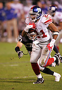 OAKLAND, CA - DECEMBER 31:  Running back Tiki Barber #21 of the New York Giants runs the ball against the Oakland Raiders at McAfee Coliseum on December 31, 2005 in Oakland, California. The Giants defeated the Raiders 30-21. ©Paul Anthony Spinelli *** Local Caption *** Tiki Barber
