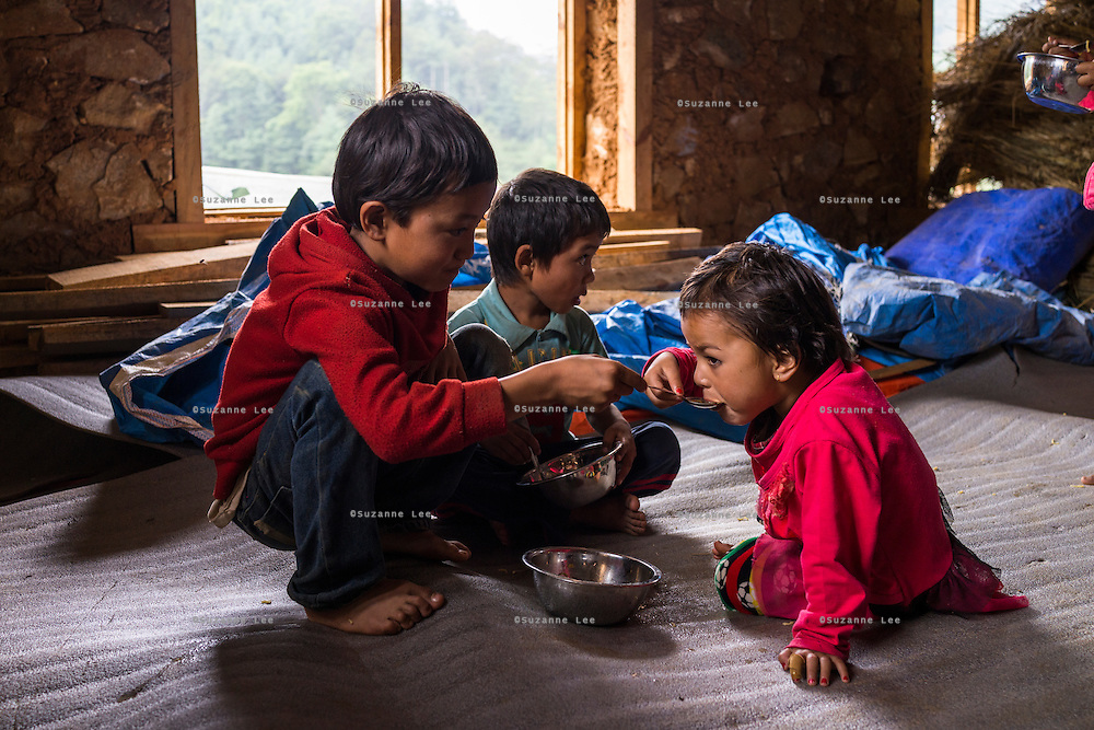 A child stays on to feed a younger child after lunch time in the SOS Children's Villages Child Care Space canteen in Rayale, Nepal on 1 July 2015. The Child Care Space was set up by SOS Children's Villages soon after the earthquake so that the children of the village can come together to play, learn, and get over the trauma of the disaster as well as get regular daily meals. This also allows their parents to be free to reconstruct their homes and go off to get rations and relief kits. Photo by Suzanne Lee for SOS Children's Villages