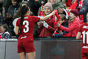 Liverpool women defender Leighanne Robe (3) hands out scarfs to young fans  during the FA Women's Super League match between Liverpool Women and Everton Women at Anfield, Liverpool, England on 17 November 2019.