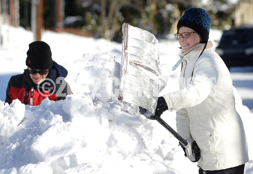 Tara Grunde-McLaughlin (right) of Newtown, Pennsylvania shovels snow rom the sidewalk while cleaning up after Winter Storm Jonas Sunday January 24, 2016 in Newtown, Pennsylvania. (Photo by William Thomas Cain)