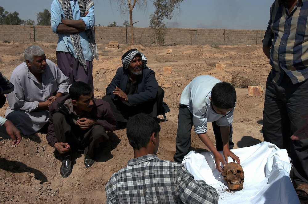 The family of Latif Ali Bati, who was arrested and disappeared in 1986, exhumes his body from the al-Karr cemetary where there are more than 1000 graves, marked only by a number, of prisoners executed by Saddam Hussein's regime..Baghdad, Iraq. 28 April 2003..Photo © J.B. Russell