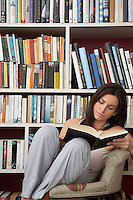 Young woman reading in chair by bookshelf