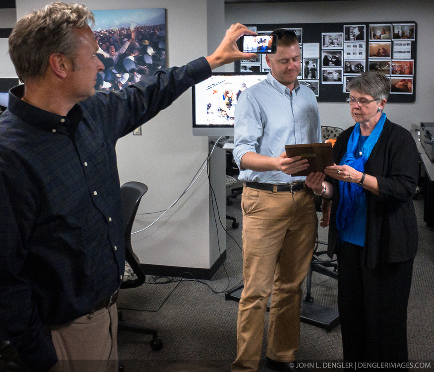 A reception was held for Rita Reed, photojournalism professor at the Missouri School of Journalism, to celebrate her retirement after 16 years of being on the faculty. <br /> <br /> In this photo, Reed (right) presents a special award to Brett Slaughter, web producer for the College Photographer of the Year Competition, for his many years of help with the contest. Holding a cellphone camera for a Facebook live session is Brian Kratzer, assistant professor of photojournalism. Reed has been the director of the College Photographer of the Year Competition for many years and in recent years has shared that role with co-director with Jackie Bell, associate photojournalism professor.<br /> <br /> The event was held on May 10, 2017 in the Cliff and Vi Edom Photojournalism Lab in Lee Hills Hall on the University of Missouri campus in Columbia, Mo.<br /> <br /> The following is from Reed&rsquo;s bio posted on the Missouri School of Journalism website: &quot;Rita Reed joined the photojournalism faculty in 2001 after 20 years as a working photojournalist with Star Tribune in Minneapolis and The Gazette in Cedar Rapids, Iowa. She has worked not only on local, regional and national stories, but also internationally in Haiti, Bolivia, Colombia, Taiwan, China and the countries of the former Eastern Block.<br /> <br /> Reed holds a master&rsquo;s degree in journalism from the University of Missouri and an undergraduate degree from Southwest Missouri State University. She was the 1993 recipient of the Nikon Sabbatical Grant for Documentary Photography for the completion of work on a photographic book about gay and lesbian teenagers. Reed maintains an interest in and concern for adolescents and the issues they face. She is the director of the College Photographer of the Year competition.&rdquo;