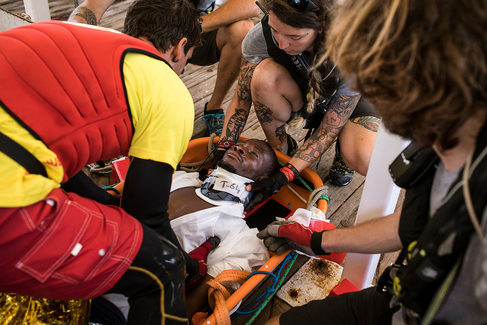 June 29th, 2017, Central Mediterranean. Reception and preparation to lower him to the hospital on board. The patient was unconscious and had seizures. Evacuation of Samuel Osei, a 36-year-old man from Ghana severely sick after being rescued in the sea. NGO Proactiva Open Arms in their 20th rescue mission in the Central Mediterranean Sea on board of Golfo Azzurro vessel (photo Edu Bayer)