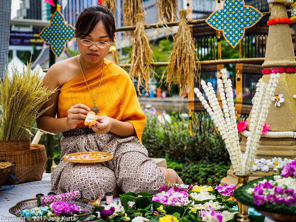 "08 APRIL 2017 - BANGKOK, THAILAND: A woman makes traditional Thai Songkran crafts at the ""Amazing Songkran"" festival in Benchasiri Park in Bangkok. Songkran is celebrated in Thailand as the traditional New Year's Day from 13 to 16 April. Songkran is in the hottest time of the year in Thailand, at the end of the dry season and provides an excuse for people to cool off in friendly water fights that take place throughout the country. Songkran has been a national holiday since 1940, when Thailand moved the first day of the year to January 1. Songkran 2017 is expected to be more subdued than Songkran usually is because Thais are still mourning the October 2016 death of revered King Bhumibol Adulyadej.       PHOTO BY JACK KURTZ"