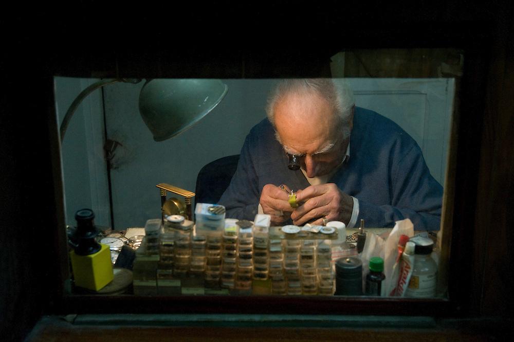 Frankrijk, Parijs, 30 jan 2010.Horlogemaker aan het werk in zijn atelier. Door het raam kan hij zijn kleine winkel in de gaten houden...Foto (c)  Michiel Wijnbergh