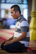 17 DECEMBER 2012 - SINGAPORE, SINGAPORE: A man prays in Sultan Mosque in Singapore. The Sultan Mosque is the focal point of the historic Kampong Glam area of Singapore. Also known as Masjid Sultan, it was named for Sultan Hussein Shah. The mosque was originally built in the 1820s. The original structure was demolished in 1924 to make way for the current building, which was completed in 1928. The mosque holds great significance for the Muslim community, and is considered the national mosque of Singapore. It was designated a national monument in 1975.     PHOTO BY JACK KURTZ