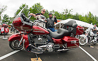 Harley Davidson Motor Company technician Tim Torgerson goes over route instructions to Desi Alvarez prior to taking out a Road Glide Ultra from the Harley Davidson free demo ride setup at Hart's Turkey Farm's parking lot in Meredith Monday morning.    (Karen Bobotas/for the Laconia Daily Sun)