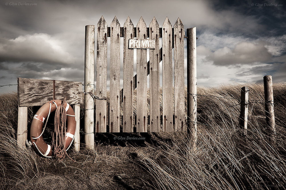 A weathered wooden gate reads Private to stop trespassing at an exposed headland at Cymyran, Holy Island, West Anglesey, Wales