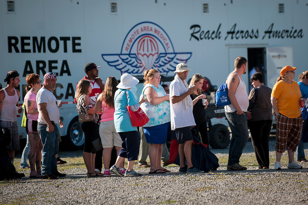 People stand in line to be processed in the triage tent at the 16th annual Remote Area Medical (RAM), clinic in Wise, Virginia, U.S., on Friday, July 17, 2015. RAM is a nonprofit that delivers free medical care to people living in rural areas. On RAM's first day it took in over 1,600 patients, setting an opening day record. By noon on Saturday, RAM had taken in another 1,000 patients. One woman's life may have been saved on Friday after women's health physicians determined she had a dangerous ectopic (tubal) pregnancy. She was taken to an area hospital for further care. In recent years, 2,500 to 3,000 people have sought care at this clinic at the fairgrounds. Photographer: Pete Marovich/Bloomberg