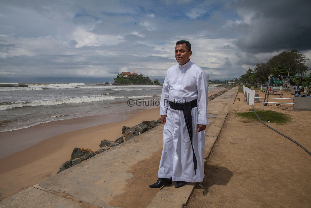 Father Damian, priest of Matara, in front of Matara's beach,devastated by the tsunami of December 26, 2004