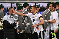 FUSSBALL  INTERNATIONAL TESTSPIEL  IN DORTMUND  22.03.2017 Deutschland - England           Lukas Podolski (Mitte) watscht Chef-Zeugwart Thomas Mai (Mitte) ab. Mats Hummels (re, alle Deutschland) ist amuesiert