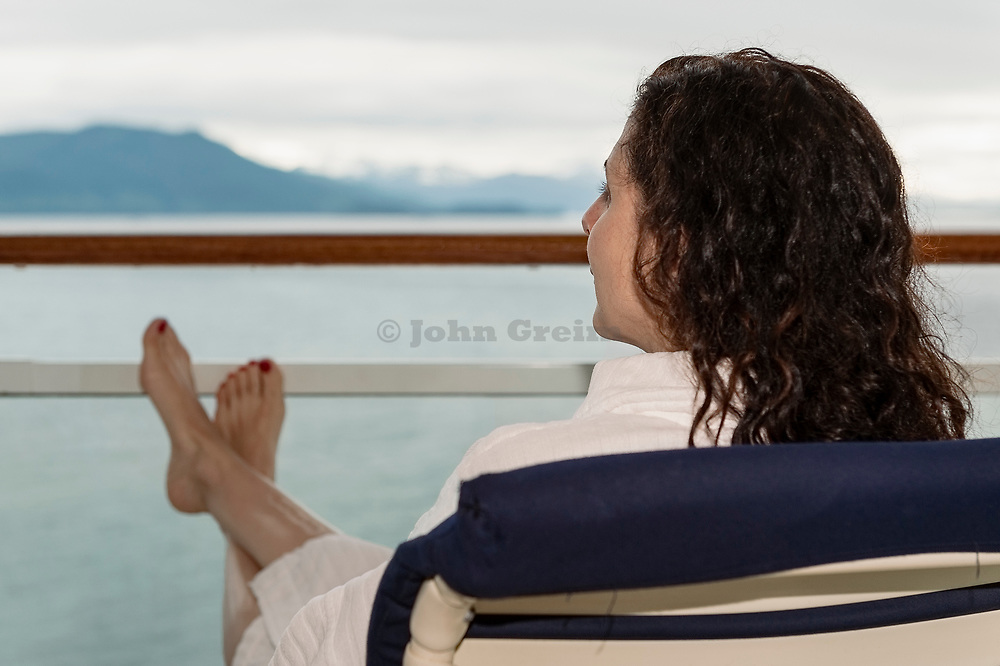 Woman enjoying the view from her cruise ship balcony.