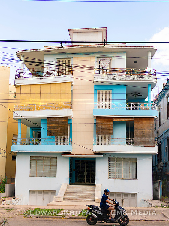 A scooter passing by a Modernist Vedado apartment with roll shutters and a faded blue paint job.