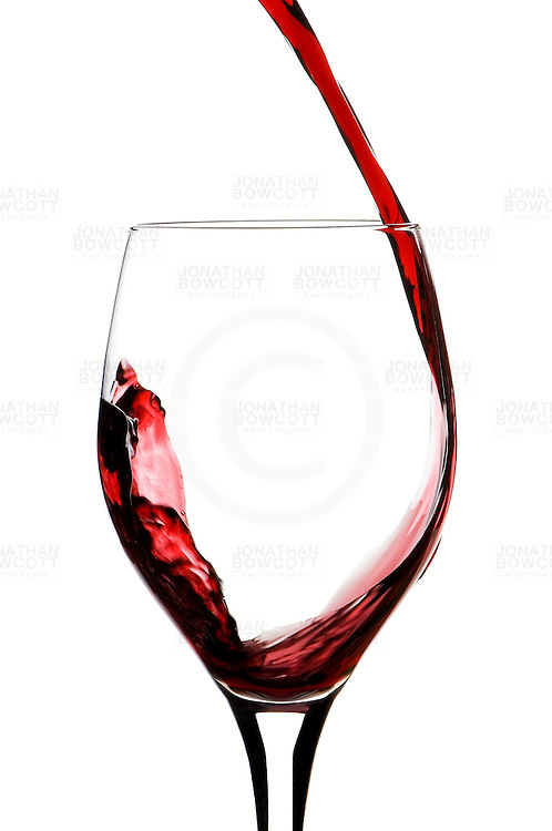 Flow of red wine being poured into a glass captured by Bristol based product photographer Jonathan Bowcott