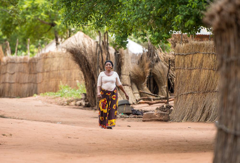 Zambian women in traditional patterned skirt walks by herself through village, Mukuni Village, Zambia