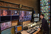 Aurelien Pasquet, stage manager in charge of sound, light, video, computers and telephones, in the production office in the tribune (first floor gallery of the nave) at the Cathedrale Notre-Dame de Paris, or Notre-Dame cathedral, built 1163-1345 in French Gothic style, on the Ile de la Cite in the 4th arrondissement of Paris, France. This is the place where all recordings are controlled, which are regularly broadcast on Radio Notre Dame and KTO Television. Picture by Manuel Cohen