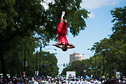 A member of the Jesse White Tumblers performs a flip high above King Drive during the Bud Billiken Parade on August, 12 2017.