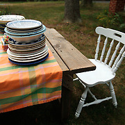 An empty chair and picnic table with many empty dishes waits outside.