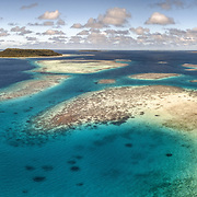 This is an aerial view of the coal reef extending from Mounu Island toward Euakafa Island, which is visible in the background. The passage seen in this image is frequently used by boats to pass through the reef. It is deep enough for humpback whales to pass through on occasion.