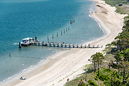 Harkers Island Ferry arriving at Harkers Island with passengers wallking on dock to beach, as seen from above atop the Cape Lookout Lighthouse.