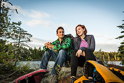 A young couple take a break from paddling a canoe on Long Pond in Maine's north woods. Near Greenville, Maine.