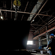 Operator using overhead crane to lift steel plate in factory.