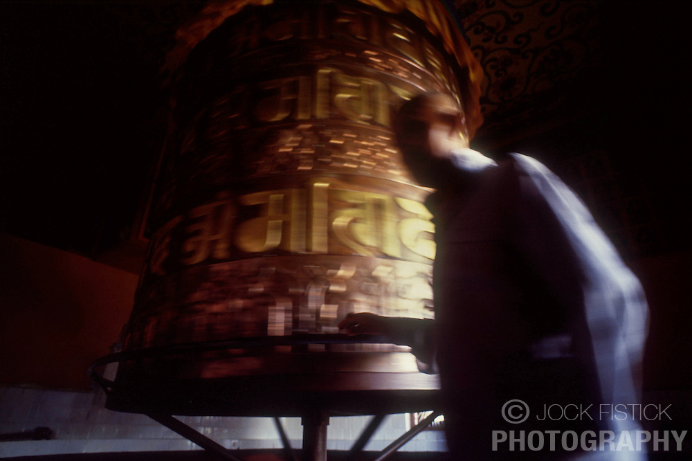 POKHARA, NEPAL - A man walks around a giant prayer wheel near Pokhara, Nepal, in the foothills of the Annapurna mountain range. (Photo © Jock Fistick)