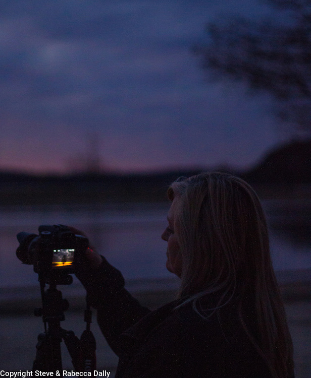 Woman photographing Norfork Lake sunset, with storm clouds coming in.<br />