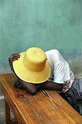 Femme faisant une sieste lors d'une assemble?e de paysannes-commerc?antes..Petite-Rivie?re de Nippes, Hai?ti,.A peasant haitian woman doing a siesta at a table..Lorsque j'aperc?ois cette femme paysanne au chapeau de paille faisant une sieste assise a? une table, je sais que j'ai devant moi une sce?ne tre?s photoge?nique, un cadeau du ciel comme il en arrive parfois lorsqu'on photographie et observe l'environnement et qu'il s'agit simplement de cueillir. J'aime cette photo pour sa simplicite?, l'e?quilibre des formes, le contraste et la douceur des teintes qui me font penser a? un tableau de nature morte. J'aime aussi la se?re?nite? qu'elle communique. Nous sommes dans le village au jolie nom de Petite-Rivie?res-des-Nippes, dans la belle re?gion du sud-ouest d'Hai?ti..