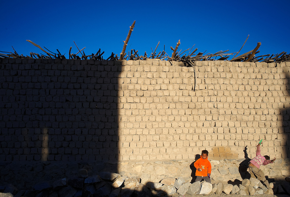 Two kids playing with plastic guns in front of a wall made of mud-bricks.<br /> <br /> In Ladakh region almost all the houses are made up of mud-bricks which keeps the house warm during the harsh winters when these areas are fully covered in snow.