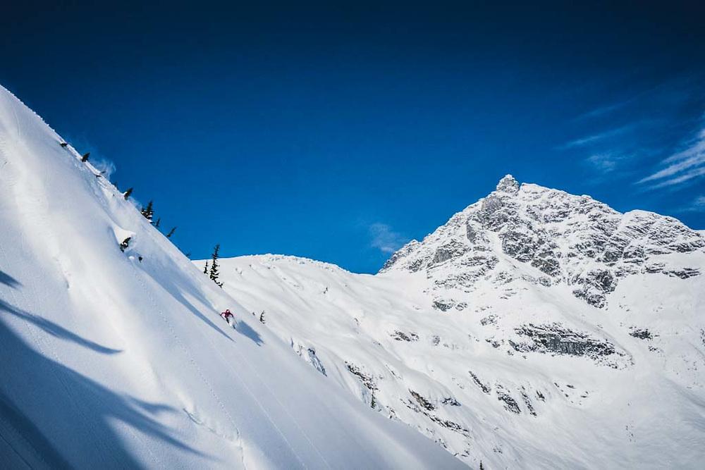 Dropping! Erme Catino skiing below Loft Peak Glacier, howson Range, British Columbia.