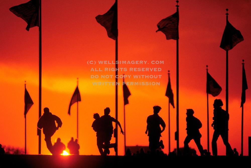 Image of boys running with U.S. flags waving at the Washington Monument, Washington DC, at sunset