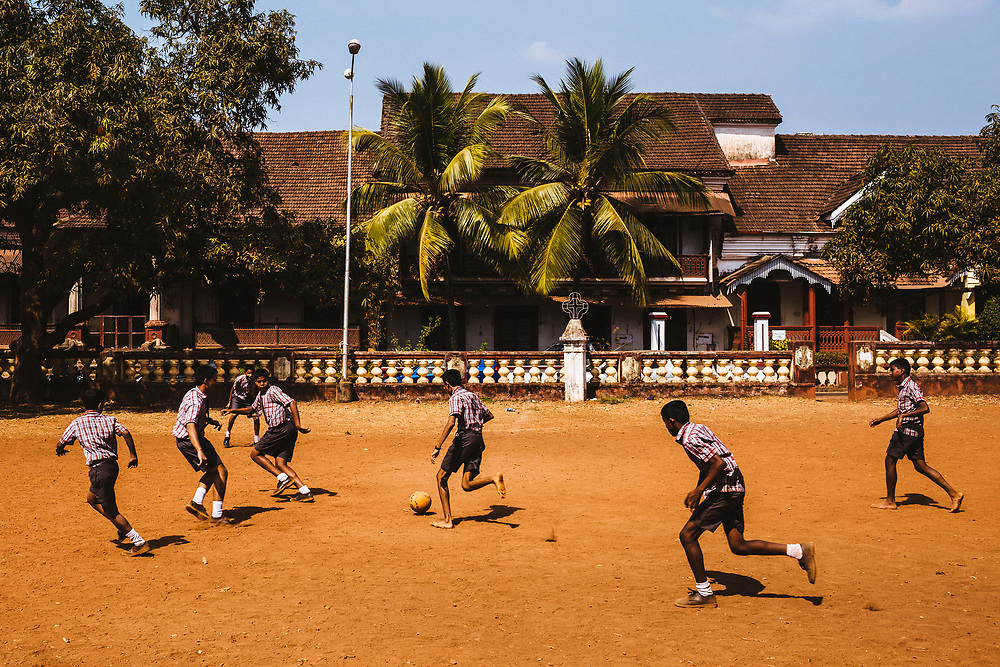 School children play a game of football with an old Portuguese mansion in the background in Margao, India.