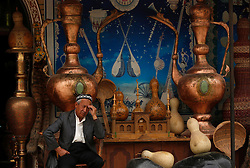 A picture made available on 31 May 2013 of a merchant of the Uighur  ethnic group sitting out his shop selling bronze wares in the old town of Kashgar, western edge of China's Xinjiang Uighur Autonomous Region, China 24 May 2013. Uighurs, a Muslim ethnic minority group in China, make up about 40 per cent of the 21.8 million people in Xinjiang, a vast, ethnically divided region that borders Pakistan, Afghanistan, Kazakhstan, Kyrgyzstan and Mongolia. Other ethnic minorities living in here include the Han Chinese, Kyrgyz, Mongolian and Tajiks people. In the restive region of Kashgar, western end of Xinjiang where the North and South Silk road meets, Uighurs comprise of more than 90 per cent of the 3.9 million population. Most practice a moderate form of Islam and religion is a major part of most ordinary Uighurs' lives. Tensions have been high between the Uighurs and the dominant Han Chinese as Uighurs complain of cultural and religious repression and claim that Han Chinese migrants enjoy the main benefits of development in the oil-rich but economically backward region.
