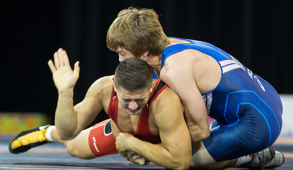 Alvis Almendra (L) of Panama taps out to concede the gold medal to Andrew Bisek of the United States  in the 75kg class of the men's greco-roman wrestling at the 2015 Pan American Games in Toronto, Canada, July 15,  2015.  AFP PHOTO/GEOFF ROBINS