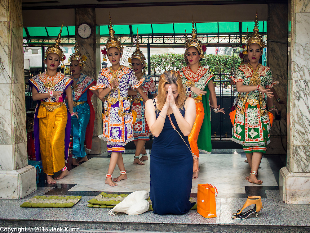27 JANUARY 2015 - BANGKOK, THAILAND: A woman prays while Aspara style dancers perform for her at Erawan Shrine in Bangkok. After months of relative calm following the May 2014 coup, tensions are increasing in Bangkok. The military backed junta has threatened to crack down on anyone who opposes the government. Relations with the United States have deteriorated after Daniel Russel, the US Assistant Secretary of State for Asian and Pacific Affairs, said that normalization of relations between Thailand and the US would depend on the restoration of a credible democratically elected government in Thailand.      PHOTO BY JACK KURTZ