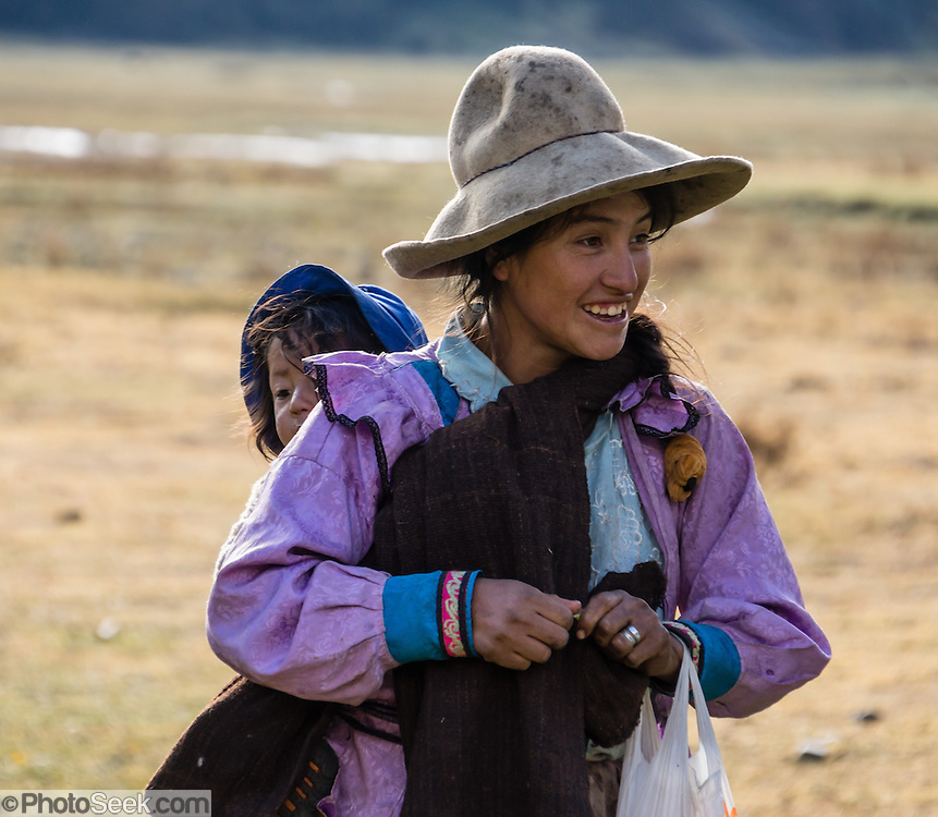 Campesino woman carries a child in a sling on her back at Camp 4 at 3700 meters elevation in Jancapampa Valley, in the Cordillera Blanca, Andes Mountains, Peru, South America. Day 4 of 10 days trekking around Alpamayo in Huascaran National Park.