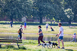 © Licensed to London News Pictures. 26/04/2020. London, UK. Members of the public go out to enjoy the warm weather on Wimbledon Common during lockdown where temperatures are expected to reach 21c. London has seen an increase in traffic and busier High Streets as more shops and cafes start to open up during the coronavirus pandemic crisis. Photo credit: Alex Lentati/LNP