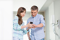 Father and daughter using smart phone at home