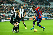Wilfried Zaha (#11) of Crystal Palace attempts to find a way beyond Javi Manquillo (#19) of Newcastle United and Fabian Schar (#5) of Newcastle United during the Premier League match between Newcastle United and Crystal Palace at St. James's Park, Newcastle, England on 21 December 2019.
