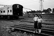 "Portrait of two kids in front of the hospital train Lifeline express stopped in Kumardubi town, Jharkhand state in India. India Poverty in Jharkhand is generally associated with inaccessibility, and the lack of basic facilities and economic opportunities. Chronic poverty seems to be disproportionately high among the historically marginalized groups, especially the tribal population.<br /> --<br /> (Bura Sapna minds ""nightmare"" in Hindi.) <br /> <br /> India, with its 1,25 billion people is the second most populous country in the world and one of the fastest booming economies. However, despite the incredible economic growth, it has still the largest share of poor people in the world: 42 per cent of its population still lives below the poverty threshold (1,25 US dollars per day).  India is mainly rural, with two thirds of its population living in rural areas, where the access to health services is very limited and obsolete: hospitals have scarce resources and waiting lists can be eternal. Significant disparities among states and social groups make the poor, tribes, girls and lower casts the most vulnerable and affected by the lack of a proper care.  This work is a journey inside a hospital train traveling through the poorest Indian states, exploring the most isolated hospitals where extreme poverty afflicts without mercy and affects more than half of the population. <br /> --"
