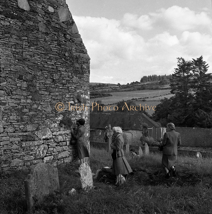 Cemetry at Ballyvoureen, Co Cork .14/07/1958. Ballyvourney is a Gaeltacht village in south-west County Cork, Ireland. Ballyvourney, Baile Bhuirne is a small village in Co. Cork that shelters a locally famous pilgrimage named after a supposed sixth-century Abbess: St. Gobnet. Gobnet, who may have been the brother of a more senior contemporary saint, Abban is generally depicted with a bee-hive, a reference to a story in which she defended herself and her followers from a group of raiders through prayer and the judicious application of bee stings! In the early fifties it was decided by the people of Ballyvourney that a statue of St Gobnet should be erected close to the location of a holy well and a circular stone structure known as St Gobnet's House or Kitchen and long supposed to be the foundations of a round tower. Ballyvourney During construction of the statue a crucible was found and it was decided that M.J. O'Kelly from University College Cork (excavator of Newgrange) should be invited to carry out an archaeological excavation.