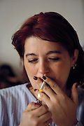"Arina Demirovic's first cigarette of her chain-smoking day. Smoking is quite prevalent in Sarajevo. Though ""no smoking"" signs abound, one can't see them through the smoke in most public places, Bosnia and Herzegovina. From coverage of revisit to Material World Project family in Sarajevo, Bosnia & Herzegovina, 2001. ©2005 Hungry Planet: What the World Eats"