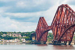View of historic Forth Railway Bridge and village of North Queensferry from South Queensferry in Scotland, United Kingdom.