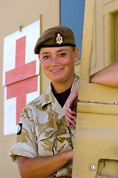 A British soldier, a female medic with the Muliti National Division in beret and desert camouflage uniform stands beside a military ambulance at Basra Air Station during Op Telic Iraq 2005