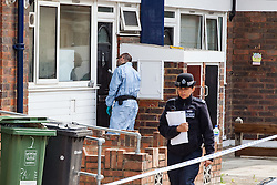 28/05/2016. London, UK. A police forensic investigator brushes a font door for finger prints on Payne Street in Deptford, south London, where a 16-year-old boy was stabbed 'repeatedly' shortly after midnight. The victim's condition is said to be 'critical', and a police cordon remains in place as investigations continue. Photo credit: Rob Pinney